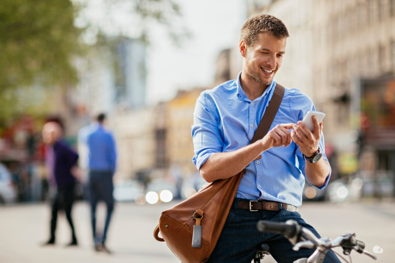 Picture of a smiling young business man who stopped his bike in the middle of a city. He is standing looking at his phone on his way to write a text message.